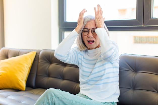 Donna graziosa di mezza età che si sente stressata e ansiosa, depressa e frustrata con un mal di testa, alzando entrambe le mani alla testa