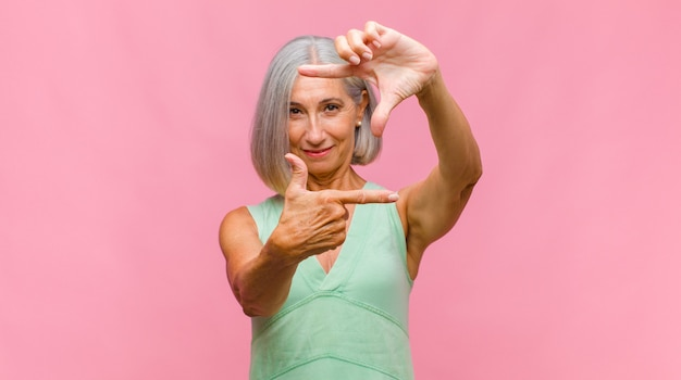 Bella donna di mezza età che si sente preoccupata, fiduciosa e religiosa, pregando fedelmente con i palmi premuti, chiedendo perdono