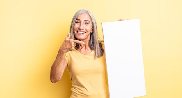 Donna graziosa di mezza età che sembra eccitata e sorpresa che indica il lato. concetto di tela vuota