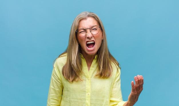 Donna graziosa di mezza età che sembra scioccata, arrabbiata, infastidita o delusa, a bocca aperta e furiosa