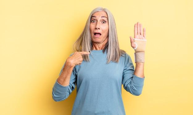 Bella donna di mezza età che sembra scioccata e sorpresa con la bocca spalancata, che indica se stessa. concetto di fasciatura per le mani
