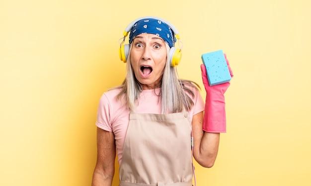 Bella donna di mezza età che sembra molto scioccata o sorpresa. detergente per pagliette