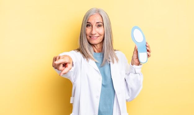 Donna graziosa di mezza età che indica alla macchina fotografica che ti sceglie. concetto di podologo