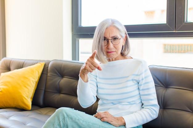 Donna graziosa di mezza età che indica alla macchina fotografica con un'espressione aggressiva arrabbiata