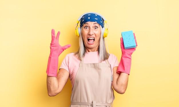 Donna graziosa di mezza età che grida con le mani in aria. detergente per pagliette