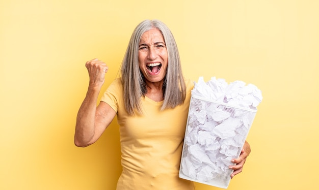 Bella donna di mezza età che grida in modo aggressivo con un'espressione arrabbiata. concetto di fallimento delle palle di carta