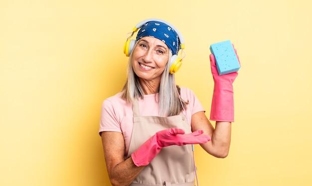 Bella donna di mezza età che sorride allegramente, si sente felice e mostra un concetto. detergente per pagliette