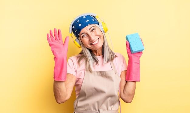 Bella donna di mezza età che sorride felicemente, agitando la mano, dandoti il benvenuto e salutandoti. detergente per pagliette