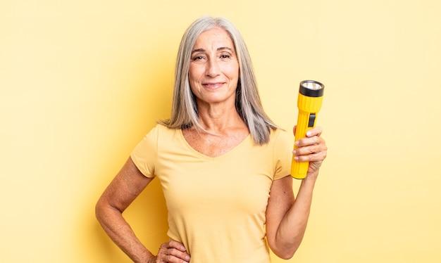 Donna graziosa di mezza età che sorride felicemente con una mano sull'anca e sicura. concetto di torcia elettrica
