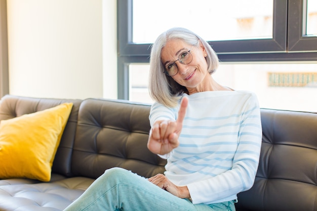Bella donna di mezza età che sorride con orgoglio e sicurezza facendo posare trionfante il numero uno, sentendosi un leader