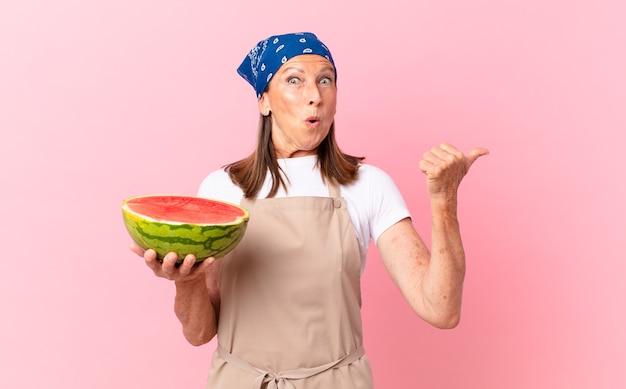 Bella donna di mezza età con un grembiule e con in mano un cocomero