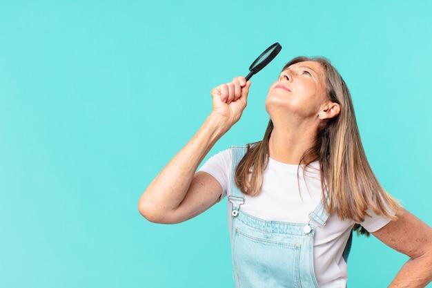 Donna graziosa di mezza età con una lente d'ingrandimento. concetto di ricerca