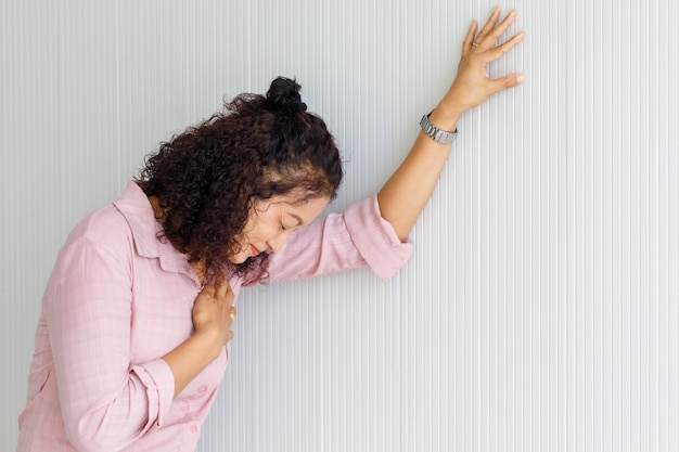 La donna asiatica anziana di mezza età interrompe il movimento e si appoggia al muro con un attacco di cuore.