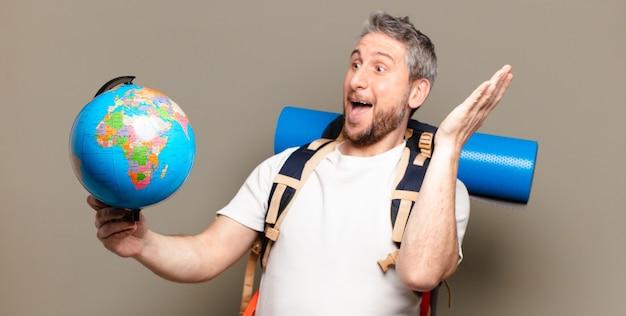 Uomo viaggiatore di mezza età con una mappa del globo del mondo