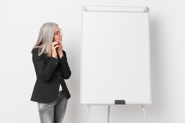 Donna di affari dei capelli bianchi di mezza età con uno spazio vuoto della copia del bordo.