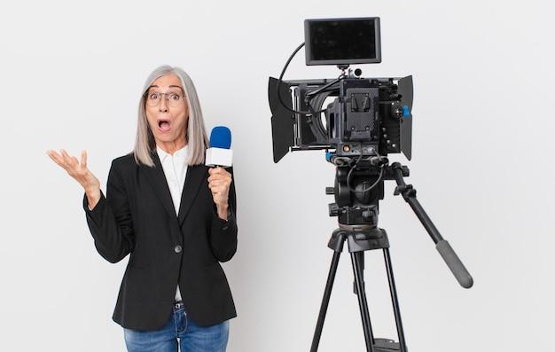 Donna di mezza età con i capelli bianchi stupita, scioccata e stupita con un'incredibile sorpresa e con in mano un microfono. concetto di presentatore televisivo