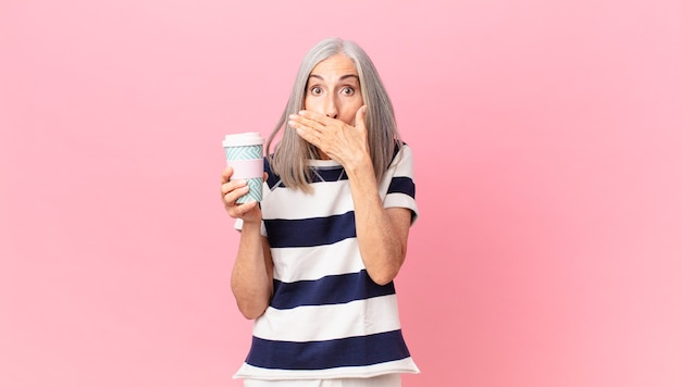 Donna di mezza età con i capelli bianchi che copre la bocca con le mani con uno shock e tiene in mano un contenitore di caffè da asporto