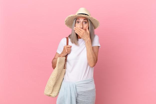 Donna di mezza età capelli bianchi che copre la bocca con le mani con uno scioccato. concetto di estate