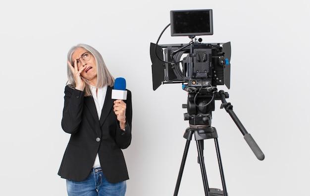 Donna di mezza età con i capelli bianchi che si sente annoiata, frustrata e assonnata dopo una noiosa e con in mano un microfono. concetto di presentatore televisivo