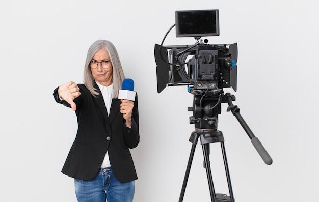 Donna di mezza età con i capelli bianchi che si sente croce, mostra i pollici in giù e tiene in mano un microfono. concetto di presentatore televisivo