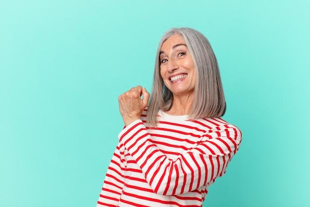 Donna di mezza età capelli bianchi sentirsi felice e affrontare una sfida o festeggiare