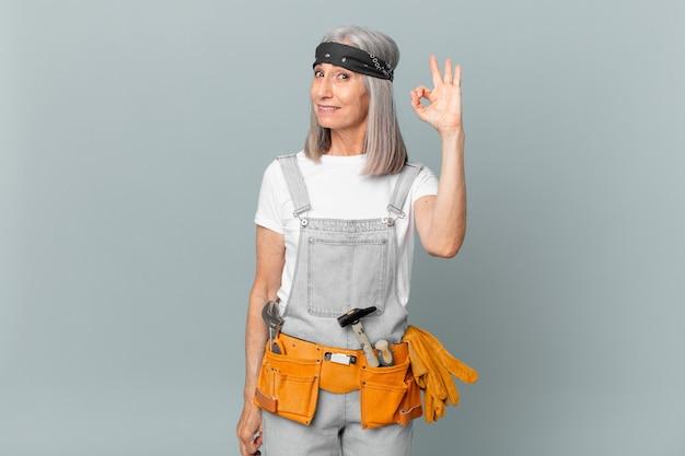 Donna di mezza età con i capelli bianchi che si sente felice, mostra approvazione con un gesto ok e indossa abiti da lavoro e strumenti. concetto di pulizia