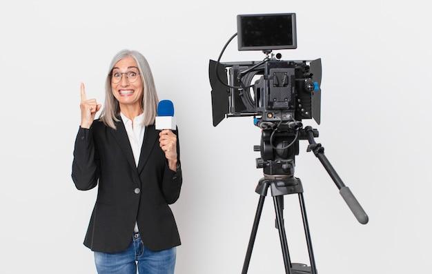 Donna di mezza età con i capelli bianchi che si sente un genio felice ed eccitato dopo aver realizzato un'idea e aver tenuto in mano un microfono. concetto di presentatore televisivo