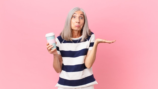Donna di mezza età con i capelli bianchi che si sente perplessa e confusa e dubita e tiene in mano un contenitore di caffè da asporto
