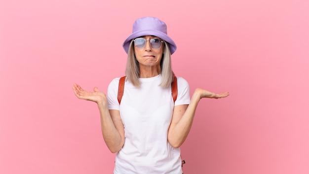 Donna di mezza età con i capelli bianchi sentirsi perplessa, confusa e dubbiosa. concetto di estate