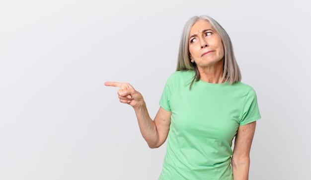 Donna di mezza età con i capelli bianchi che si sente triste, sconvolta o arrabbiata e guarda di lato e indica di lato