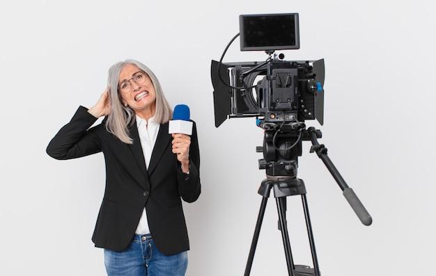 Donna di mezza età con i capelli bianchi che si sente stressata, ansiosa o spaventata, con le mani sulla testa e con in mano un microfono. concetto di presentatore televisivo