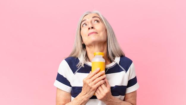 Donna di mezza età con i capelli bianchi che tiene in mano un thermos di caffè