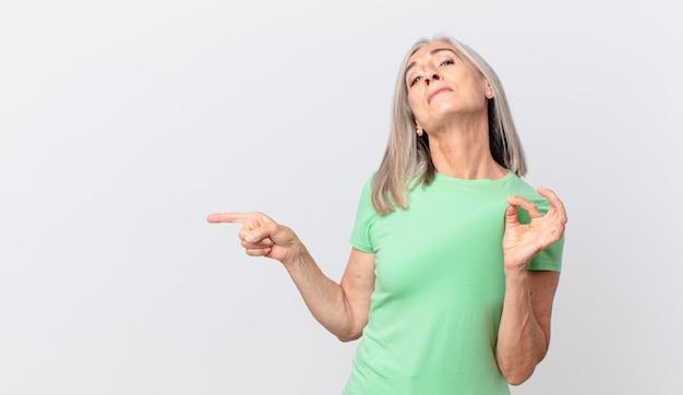 Donna di mezza età con i capelli bianchi che sembra arrogante, di successo, positiva e orgogliosa e indica il lato