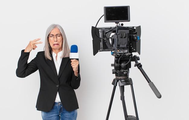 Donna di mezza età con capelli bianchi che sembra infelice e stressata, gesto suicida che fa il segno della pistola e tiene in mano un microfono. concetto di presentatore televisivo