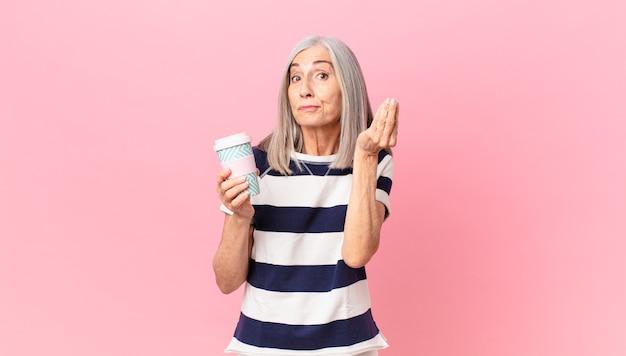 Donna di mezza età con i capelli bianchi che fa un gesto di denaro o di denaro, dicendoti di pagare e tenendo in mano un contenitore di caffè da asporto