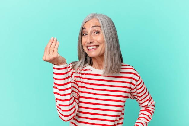 Donna di mezza età con i capelli bianchi che fa un gesto di capice o denaro, dicendoti di pagare
