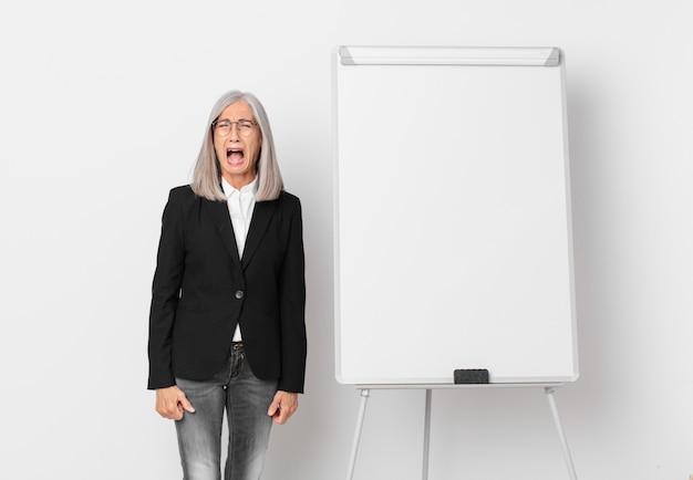 Donna di mezza età con i capelli bianchi che grida in modo aggressivo, sembra molto arrabbiata e uno spazio per la copia di bordo. concetto di business