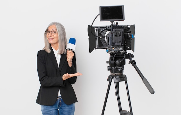 Donna di mezza età con capelli bianchi che sorride allegramente, si sente felice e mostra un concetto e tiene in mano un microfono. concetto di presentatore televisivo