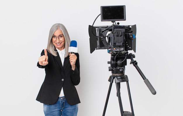 Donna di mezza età con capelli bianchi che sorride con orgoglio e sicurezza facendo il numero uno e tenendo in mano un microfono. concetto di presentatore televisivo