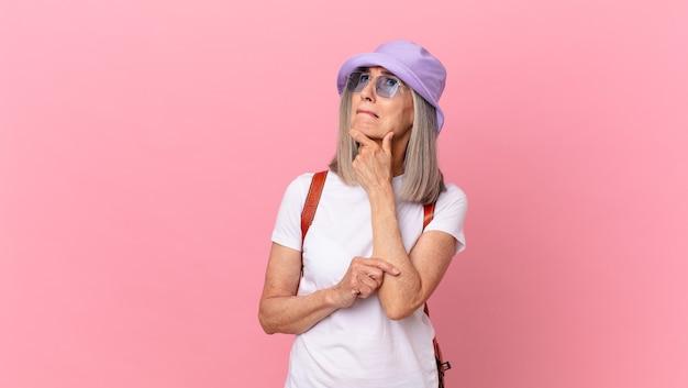 Donna di mezza età con i capelli bianchi che pensa, si sente dubbiosa e confusa. concetto di estate