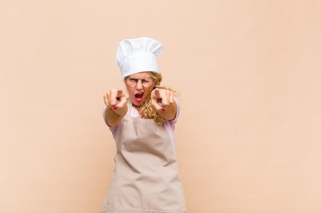 Panettiere di donna di mezza età che indica davanti con entrambe le dita e l'espressione arrabbiata, dicendoti di fare il tuo dovere