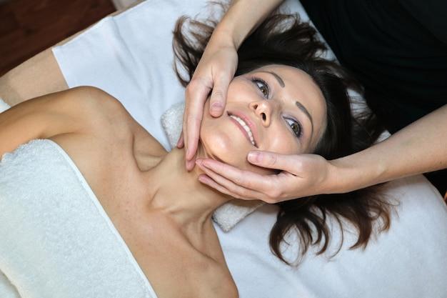 Donna di mezza età nel salone di bellezza spa, sdraiata sul lettino da massaggio. massaggio ravvicinato viso e collo. cura del corpo e del viso, assistenza sanitaria, trattamento, cosmetologia, donne mature