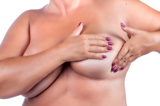 Donna di mezza età che controlla il seno (autoesame automatico) per anomalie, nodi o strani noduli per cancro al seno
