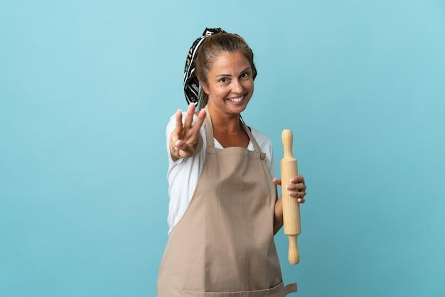Donna di mezza età in uniforme da cuoco felice e contando tre con le dita