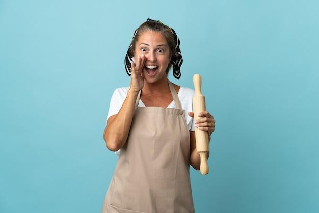 Donna di mezza età in uniforme da cuoco con espressione facciale sorpresa e scioccata