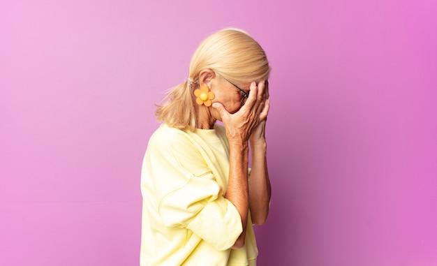 Donna di mezza età che copre gli occhi con le mani con uno sguardo triste e frustrato isolato