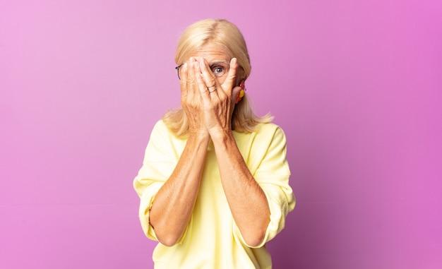 Donna di mezza età che copre il viso con le mani, sbirciando tra le dita