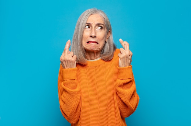 Donna di mezza età incrociando le dita ansiosamente e sperando in buona fortuna con uno sguardo preoccupato