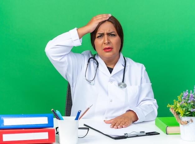 Medico donna di mezza età in camice bianco con stetoscopio che viene confuso con la mano sulla testa per errore seduto al tavolo sopra il muro verde