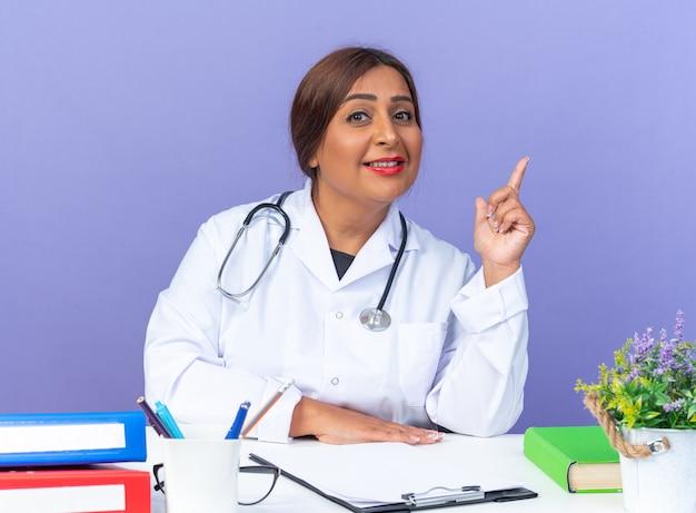Medico della donna di mezza età in camice bianco con lo stetoscopio felice e positivo che mostra il dito indice che sorride allegramente seduto al tavolo sopra la parete blu